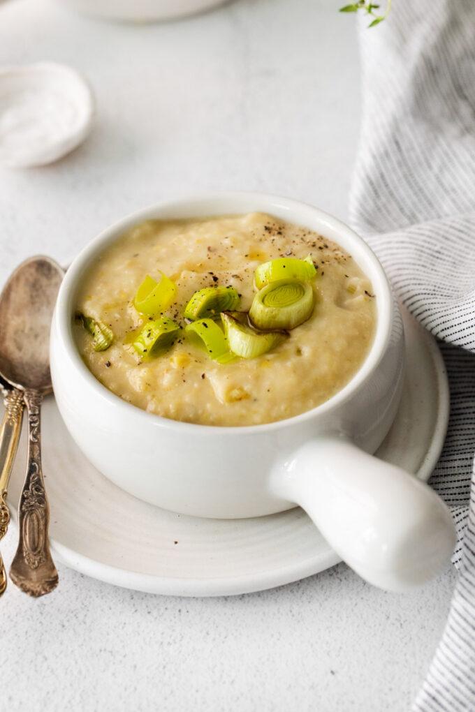 vegan potato leek soup served in a white soup bowl