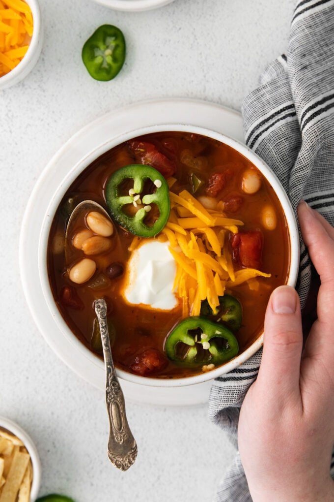 Vegetarian Taco Soup topped with sour cream, grated cheese and jalapeño slices